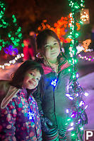 Nara And Claira Around String Of Lights